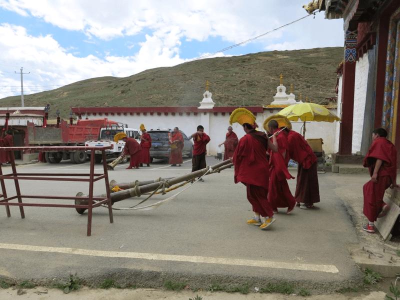 Trúbiaci budhistickí mnísi pred vstupom do kláštora v meste Litang v Tibete.
