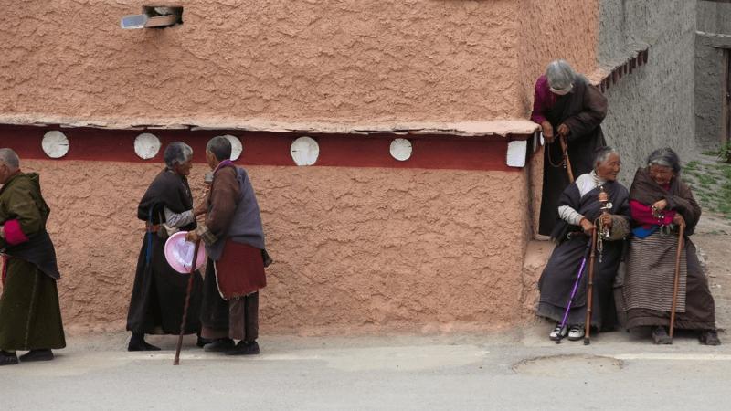 Miestni sa prizerajú na obetovávaine mäsa na lúke nedaleko kláštora v meste Litang.